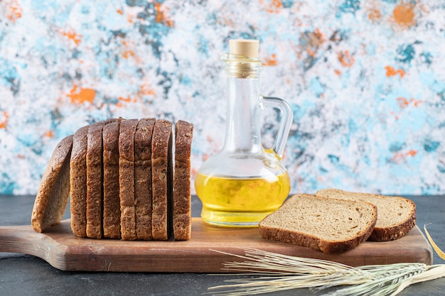 Kromki ciemnego chleba i butelka oleju na desce.