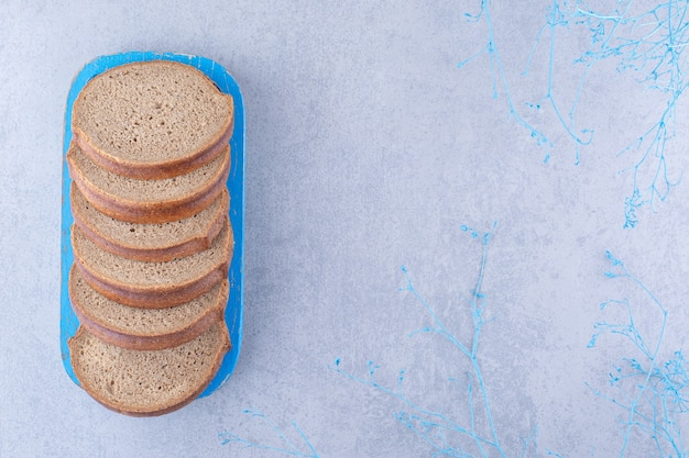 Kromki ciemnego chleba na niebieskim talerzu na marmurowej powierzchni