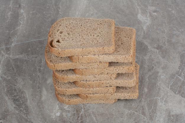 Kromki ciemnego chleba na powierzchni marmuru