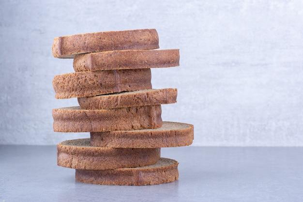 Kromki ciemnego chleba ułożone na powierzchni marmuru