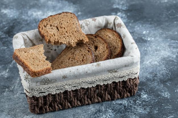 Kromki ciemnego chleba w koszu na szarej powierzchni.