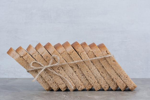 Kromki ciemnego chleba w linie na marmurowej powierzchni