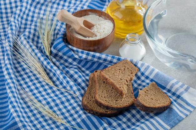 Kromki ciemnego chleba z drewnianą miską mąki.