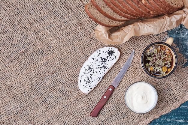 Kromki ciemnego chleba z filiżanką zupy jarzynowej.