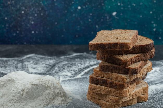 Kromki ciemnego chleba z mąką na kolorowym tle.