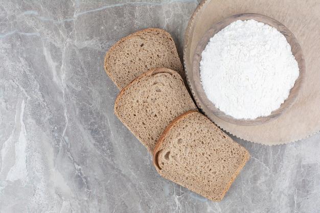 Kromki ciemnego chleba z mąką na marmurowej powierzchni