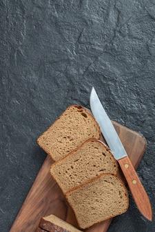 Kromki ciemnego chleba z nożem na drewnianej desce