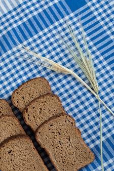 Kromki ciemnego chleba z pszenicą na obrusie.