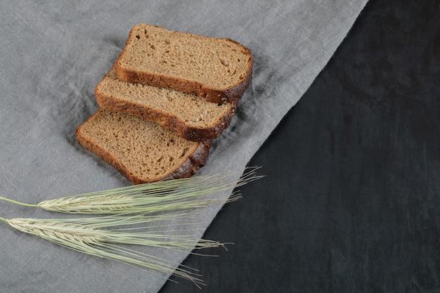 Kromki ciemnego chleba z pszenicą na szarym obrusie.