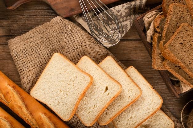 Kromki ciemnego i białego chleba z bagietką