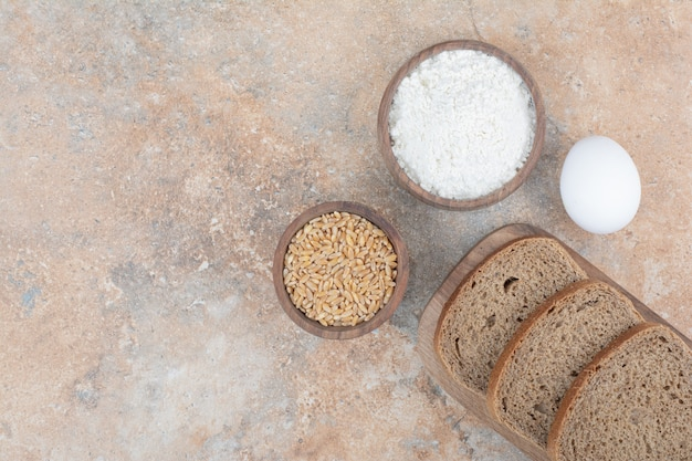 Kromki czarnego chleba, mąka, jęczmień i jajka na marmurowej powierzchni