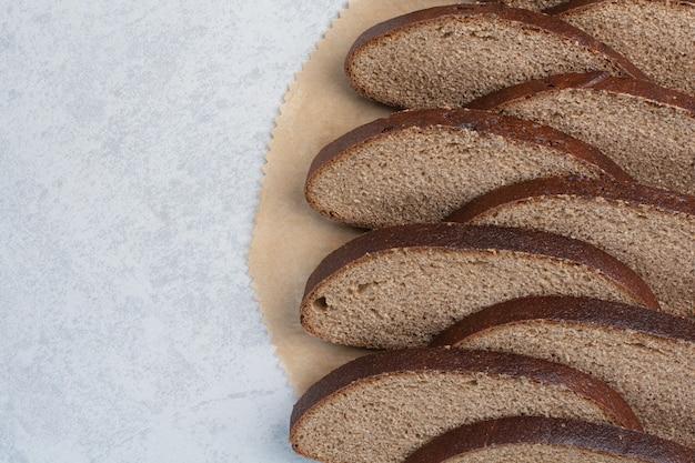 Kromki czarnego chleba na arkuszu papieru. wysokiej jakości zdjęcie