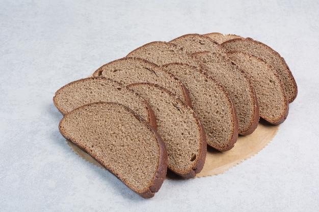Kromki czarnego chleba na arkuszu papieru