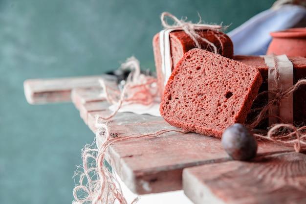 Kromki czarnego chleba owinięte białym papierem i śliwkami na drewnianym stole.