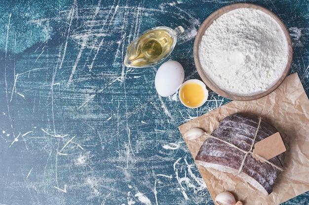 Kromki czarnego chleba z olejem na niebieskim stole, widok z góry.