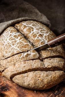 Kromki domowego chleba żytniego na desce do krojenia z nożem