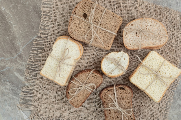 Kromki różnego rodzaju chleba związane sznurem na marmurowej powierzchni. wysokiej jakości zdjęcie