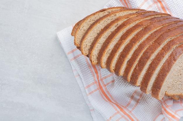 Kromki świeżego białego chleba na obrusie.