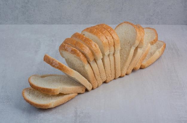 Kromki świeżego białego chleba na tle marmuru.