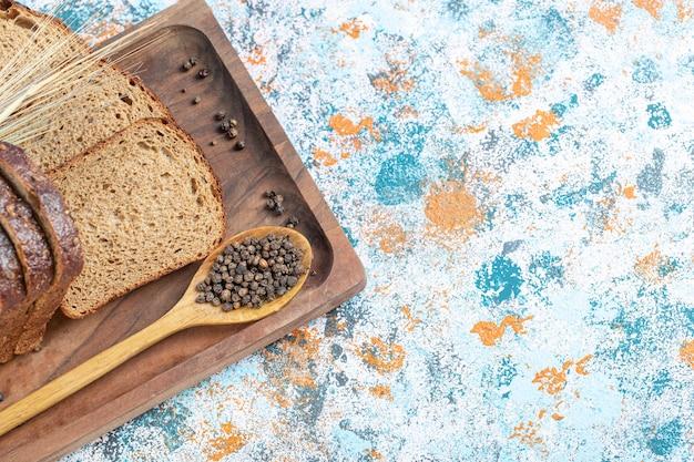 Kromki świeżego bochenka chleba na desce.