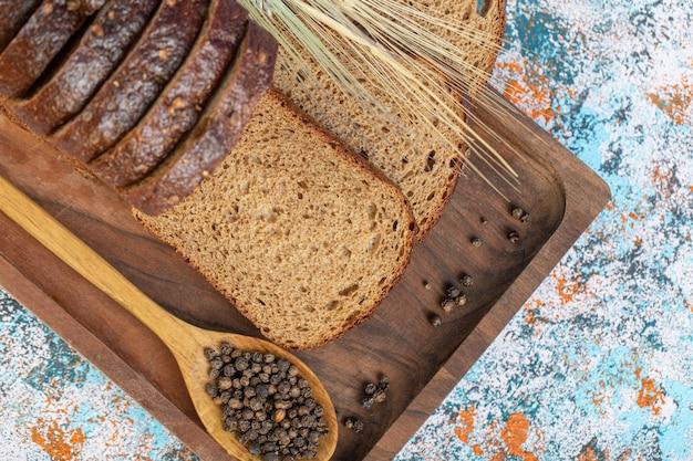 Kromki świeżego bochenka chleba na drewnianej desce