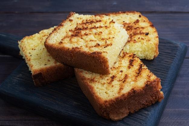 Kromki tostowy chleb pszenny na ciemnym drewnianym stole.