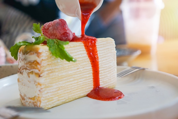 Kromkowy placek z sosem truskawkowym na białym talerzu na tle stołu - kawałek ciasta z bitą śmietaną