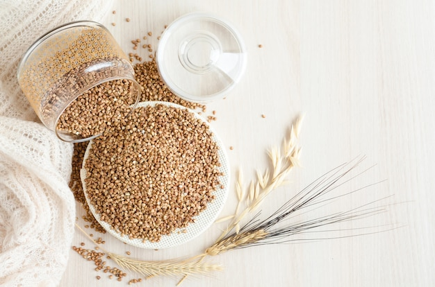 Kropiąca gryczana owsianka od szklanego słoju na białym drewnianym tle, kopii przestrzeń. zboża, ziarna, uprawy, pszenica, owies. zdrowe i pożywne jedzenie. deficyt