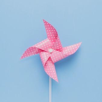 Kropkowany różowy wiatraczek na niebieskim tle