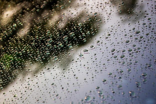 Kropla deszczu na czarnej powierzchni szkła z tłem światła słonecznego.