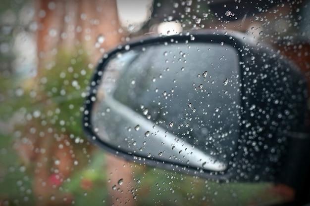 Kropla deszczu na oknie i szklanka na zewnątrz samochodu w deszczowy dzień.