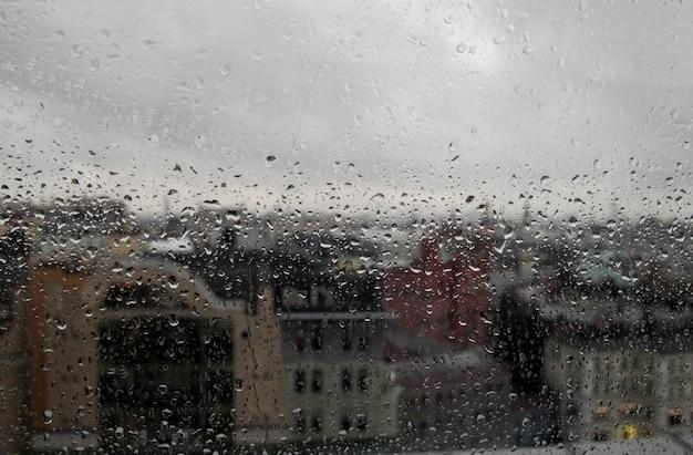 Kropla deszczu na oknie z przezroczystego szkła, odbicie rozmytego miasta i nieba, lekki bokeh z zewnątrz