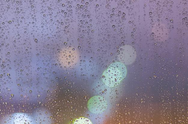 Kropla deszczu na szklanym oknie w sezonie monsunowym z kolorowym światłem bokeh z tła budynków miejskich