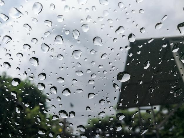 Kropla deszczu spadająca na szybę samochodu.