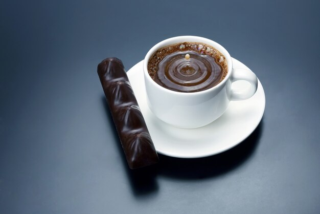 Kropla mleka wpadająca do białej filiżanki z czarną kawą