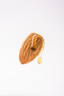 Kropla olejku ze złotych migdałów kapie z suchego owocu badam, unoszącego się w samotnym powietrzu