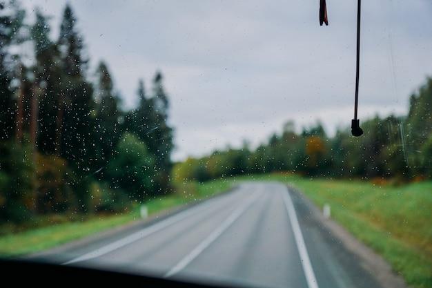 Kropla wody deszczowej na oknie widok na drogę i jesienny las