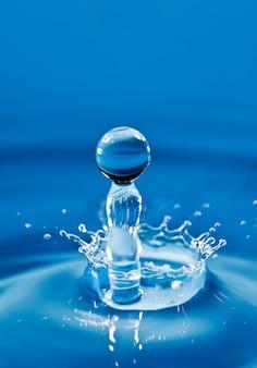 Kropla wody spada w dół, łamiąc się o kroplę