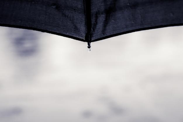 Kropla wody spada z parasola podczas deszczu. parasol chroni przed złymi warunkami pogodowymi