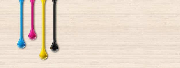 Krople atramentu 3d cmyk na białym tle na beżowym tle drewnianych. baner poziomy. ilustracja