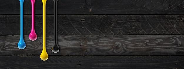 Krople atramentu 3d cmyk na białym tle na czarnym tle drewnianych. baner poziomy. ilustracja