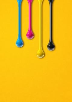 Krople atramentu 3d cmyk na białym tle na żółtym tle papieru. ilustracja