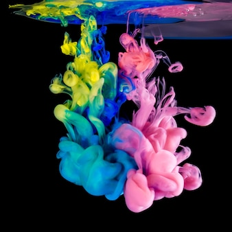 Krople atramentu kolorowego w wodzie na czarnym tle