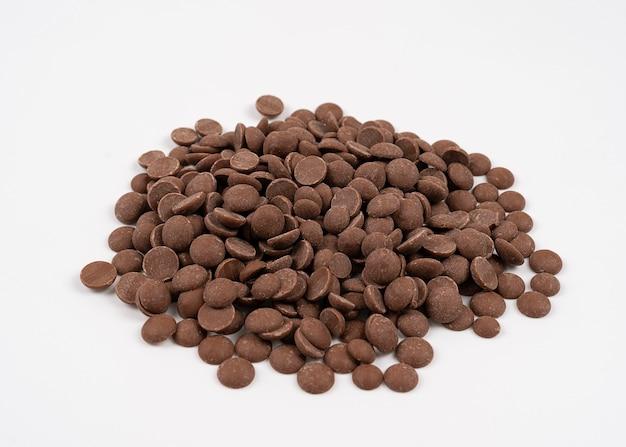 Krople czekolady mlecznej rozrzucone na białym, pojedyncze krople czekolady