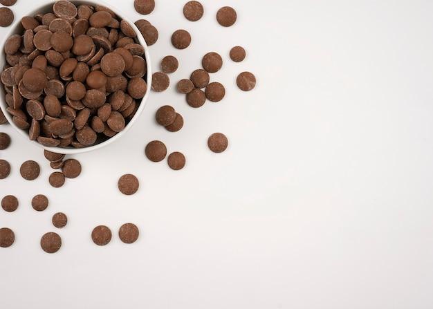 Krople czekolady w misce na białym tle.