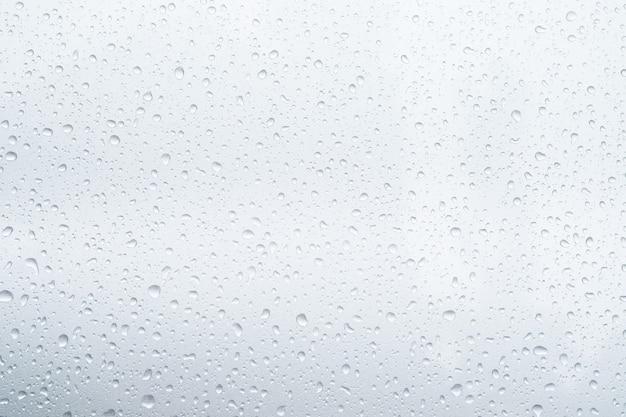 Krople deszczu i rosa. krople wody na szarym dachu samochodu po zatrzymaniu deszczu, selektywne skupienie wodoodpornej powierzchni. nieostrość. zostaw miejsce na pisanie tekstu w tle.
