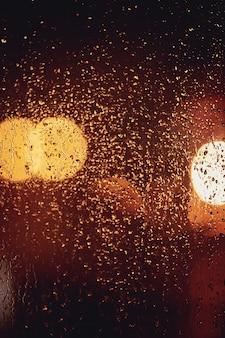 Krople deszczu i rozmyte światła przez okno.