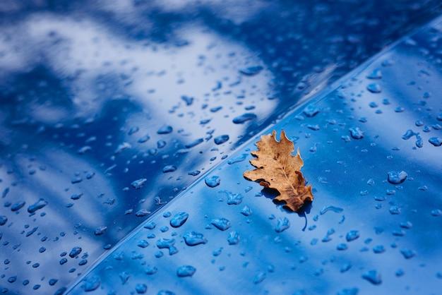 Krople deszczu i żółty suchy liść na powierzchni niebieskiego samochodu. jesienna tekstura. miękka selektywna ostrość.