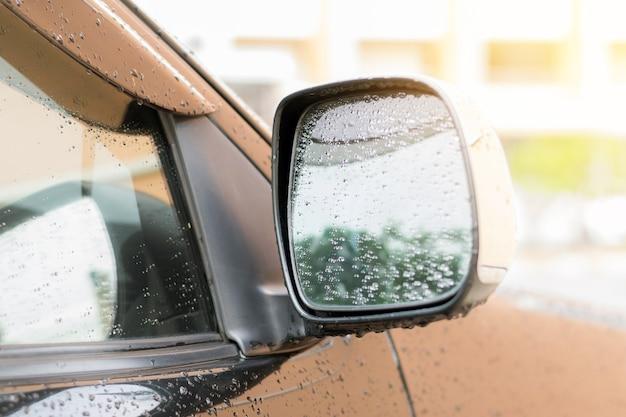 Krople deszczu na bocznym lusterku samochodu po ustaniu deszczu.