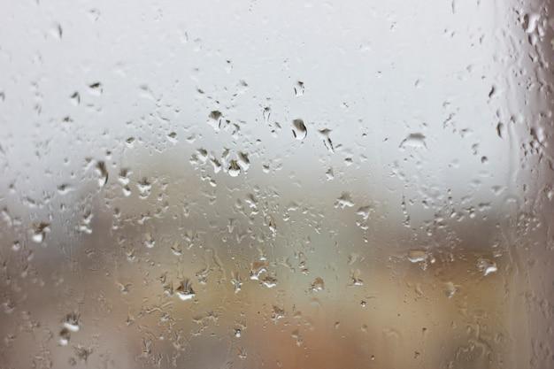 Krople deszczu na mokrym oknie. szara wilgoć